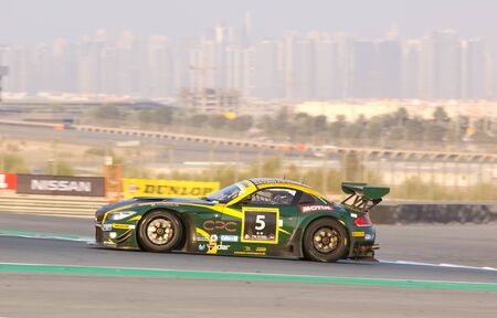 gt3: DUBAI - JANUARY 14: Car 5, a BMW Z4 GT3 with Dubai City in the background, during the 2012 Dunlop 24 Hour Race at Dubai Autodrome on January 14, 2012. Editorial