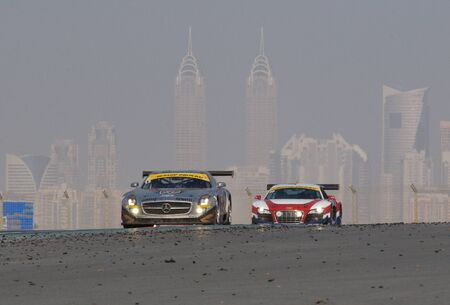 DUBAI - JANUARY 14: Mercedes SLS and Audi R8 with Dubai City in the background, during the 2012 Dunlop 24 Hour Race at Dubai Autodrome on January 14, 2012. Stock Photo - 12060229