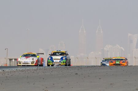 gt3: DUBAI - JANUARY 14: Porsche 997, BMW MIni and Ginetta G50 with Dubai City in the background, during the 2012 Dunlop 24 Hour Race at Dubai Autodrome on January 14, 2012.