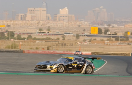 gt3: DUBAI - JANUARY 14: Car 15, a Mercedes SLS AMG GT3 with Dubai City in the background, during the 2012 Dunlop 24 Hour Race at Dubai Autodrome on January 14, 2012.