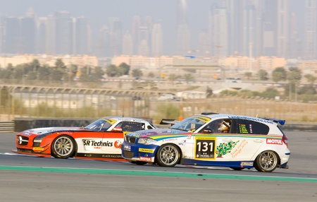 gt3: DUBAI - JANUARY 14: Mercedes SLS AMG GT3 and BMW 120D with Dubai City in the background, during the 2012 Dunlop 24 Hour Race at Dubai Autodrome on January 14, 2012. Editorial