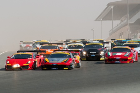 DUBAI - JANUARY 13: 75 cars coming down the dusty start-finish straight at the start of the 2012 Dunlop 24 Hour Race at Dubai Autodrome on January 13, 2012. Stock Photo - 12060286