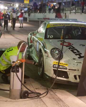 gt3: DUBAI - JANUARY 13: Pit stop at night for car 10, a Porsche 997 GT3 Cup during the 2012 Dunlop 24 Hour Race at Dubai Autodrome on January 13, 2012. Editorial
