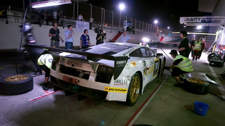 pit stop: DUBAI - 13 de enero: Coche 30, un Lamborghini Gallardo LP600 durante la parada en boxes en la noche durante el 2012 Dunlop 24 Race horas en el Aut�dromo de Dubai el 13 de enero, 2012.