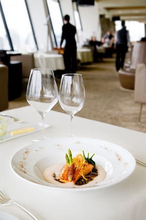 Restaurant table with salmon and green asparagus. Shallow depth of field with the food in focus and the restaurant background blurred.