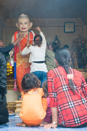 yat: PAILIN - APRIL 14: Buddhists decorating an image of Grandma Yat to show respect for the elderly at the Buddhist temple of Phnom Yat during Songkran celebration in Pailin, Cambodia on April 14, 2012.