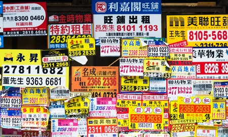 HONG KONG - MAY 13: Commercial property advertised for sale or rent on posters at a building wall in the bustling city of Hong Kong on May 13, 2012.