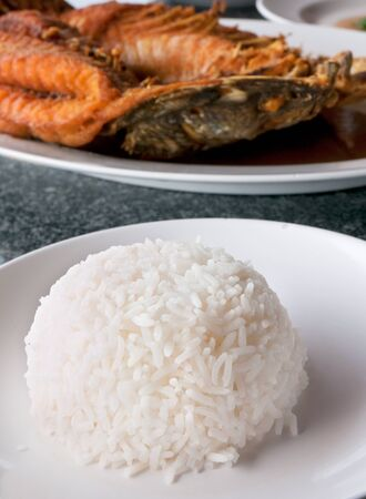 Steamed rice and fried snapper at Thai seafood restaurant  Shallow depth of field with the rice in focus  photo