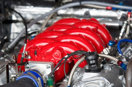 manifold: Red top of V8 racing car engine. Shallow depth of field. Stock Photo