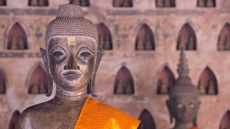 niches: Buddha Image at Wat Si Saket in Vientiane, Laos. This temple contains 6,840 Buddha images of gold, silver and bronze, many placed in niches on the wall like in the background of this photo. Shallow depth of field with the Buddha image in the foreground in