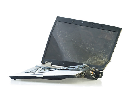 Laptop computer destroyed beyond repair in a car accident. Isolated on white background
