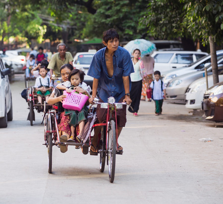 trishaw: YANGON, MYANMAR - NOVEMBER 13, 2014: Children being taken to school on cyclos. The cyclo is an important mode of transportation in the Myanmar capital, where motorbikes are forbidden. Editorial