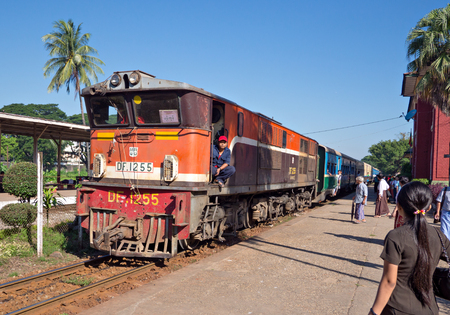 run down: Yangon, Myanmar - November 13, 2014: Train arriving at Pan Hlaing Railway Station in Yangon, Myanmar. Myanmar has an extensive railway network, but trains and staitions are mostly old and run down.