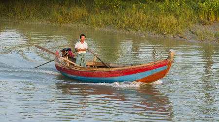 navigating: Sittwe Rakhine State Myanmar  October 16 2014: Man navigating his motorboat on a canal near Sittwe the capital of the Rakhine State in Myanmar. Editorial