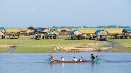 third world: Sittwe Rakhine State Myanmar  October 16 2014: Traditional boat passing a village along the Kaladan River at the Rakhine State in Myanmar.