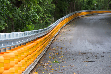guard rail: Yellow guard rail along a steep hill through a forest. Shallow depth of field with the foreground in focus. Stock Photo