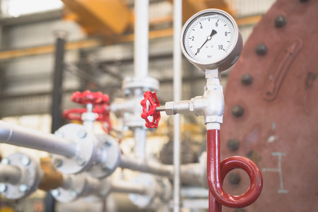 depth gauge: Pressure gauge in industrial environment. Shallow depth of field with the gauge and valve in focus. Stock Photo