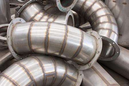componentes: piezas sin terminar para conductos de acero inoxidable industrial durante la producción. Foto de archivo