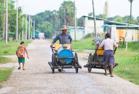 water town: Labutta Township, Myanmar - September 25, 2015: Many towns in Myanmar lack a public water supply. In Labutta, a town in the Ayeyarwady Division, vendors get water at a pump station for distribution to customers downtown.