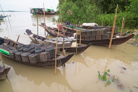 third world: Traditional, wooden boats loaded with fishing gear on the Ywe River in Labutta, a township in the Ayeyarwady Division of Myanmar. Stock Photo