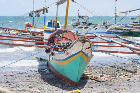 beached: Beached fishing vessels with outriggers at General Santos City, the southernmost city of The Philippines.