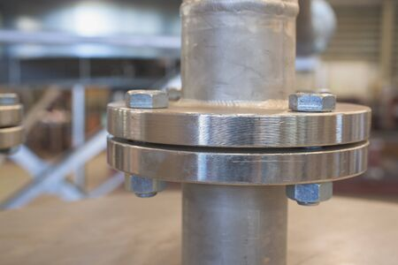 flange: Stainless steel flange. Very shallow depth of field with only the nearest part of the flange in focus with detailed horisontal lines from the lathe visible. Stock Photo