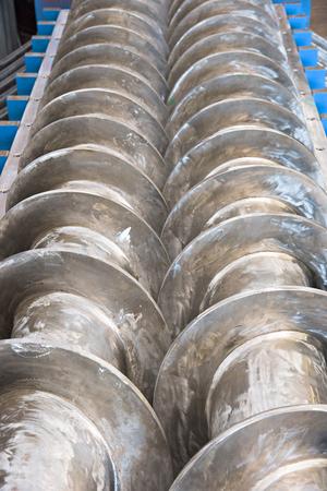 tornillos: Industrial prensa de doble husillo para el procesamiento de los residuos de la producción de carne, con las cubiertas abiertas. Poca profundidad de campo.