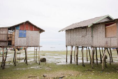 Two fishermans cottages on stilts at low tide in the village of Tinito, Maasim, Sarangani Province, The Philippines.