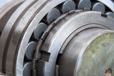 rotating: Stainless roller bearing on industrial size drive shaft. Shallow depth of field with only parts of the bearing in focus.