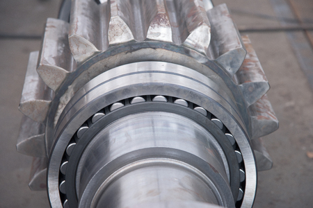 bearing: Stainless roller bearing on industrial size drive shaft. Shallow depth of field with only parts of the bearing in focus.