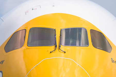 livery: Singapore - February 16, 2016: Front detail of a Boeing 787-9 Dreamliner in the livery of no frills Singapore airline Scoot during Singapore Airshow at Changi Exhibition Centre in Singapore.