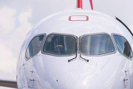 bombardier: Singapore - February 16, 2016: Front detail of a Bombardier CS100 medium range airliner in Swiss livery during Singapore Airshow at Changi Exhibition Centre in Singapore.