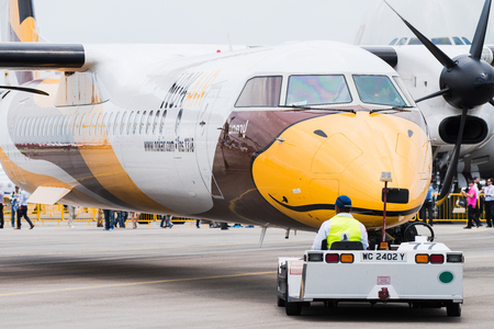 bombardier: Singapore - February 17, 2016: Front of a Bombardier Q400 NextGen in Nok Air livery being pushed into position during Singapore Airshow at Changi Exhibition Centre in Singapore.
