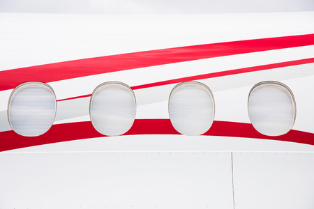 fuselage: Windows and fuselage detail of white business jet aircraft.