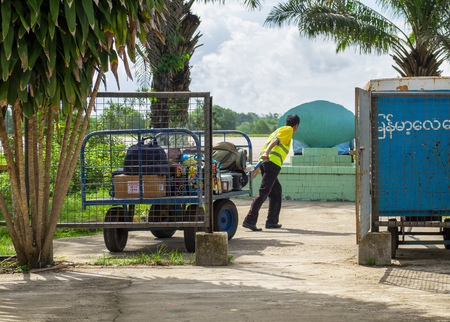 relies: Myeik, Myanmar - June 8, 2016: Due to lacking road and railway infrastructure, Myanmar relies heavily on air transport for travelling. Technology is often basic, like the baggage handling at Myeik Airport in Tanintharyi Region.