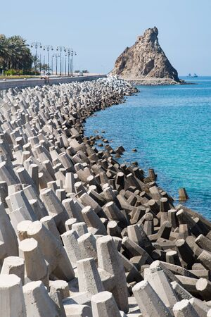 coastal erosion: Road in Muscat, Oman, protected from erosion by concrete blocks with irregular shapes.