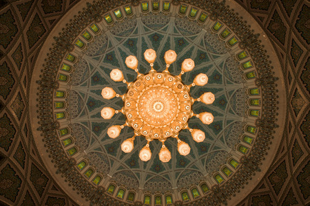 overwhelming: Muscat, Oman - February 28, 2016: The chandelier and inside of the dome of Sultan Qaboos Grand Mosque in Muscat, Oman. This is the largest and most decorated mosque in this mostly Muslim country.