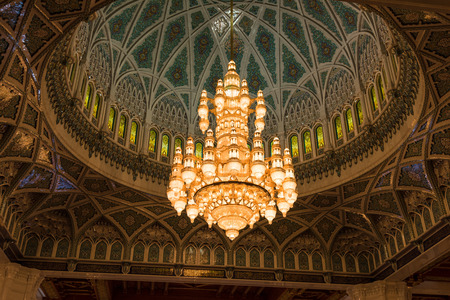 muscat: Muscat, Oman - February 28, 2016: The chandelier and inside of the dome of Sultan Qaboos Grand Mosque in Muscat, Oman. This is the largest and most decorated mosque in this mostly Muslim country.