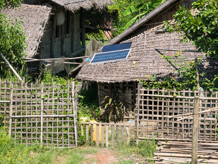 panel: Straw house with solar panel on the roof in a village at the Rakhine State of Myanmar.