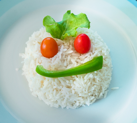 bell shaped: A portion of white rice on a plate shaped as a face using a slice of green bell pepper, two cherry tomatoes and a salad leaf.