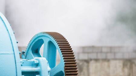 Old industrial dryer with place for text on the out of focus, foggy background. The cogwheel of the dryer in focus.