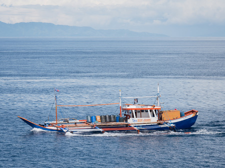 Sarangani, The Philippines - July 9, 2017: Outrigger tuna fishing boat returning to port fully loaded after a good catch at Maasim, Sarangani Province in The Philippines.