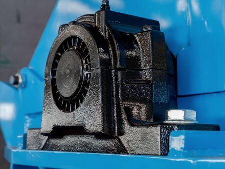 검은 공 파란색 기계에 베어링 베어링. 드라이브 샤프트의 끝이 보입니다. 하우징 상단에 윤활 니플이 있습니다.