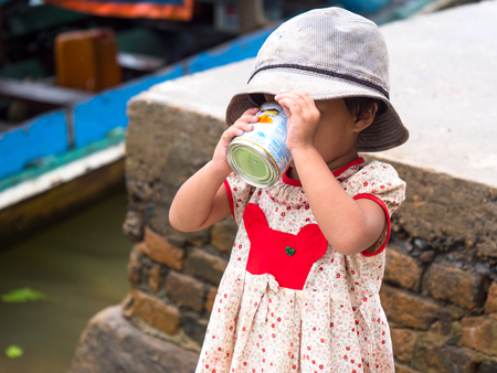 Tagu, Myanmar - November 8, 2017: Small girl drinking sweetened, condensed milk at the small town