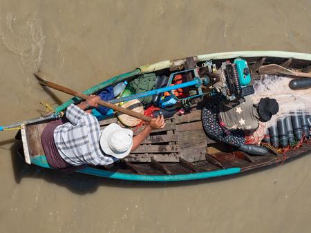 Dala, Myanmar - November 5, 2017: Aerial view of small, traditional fishing vessel with husband and wife team padling down Dala River near Yangon. Editorial
