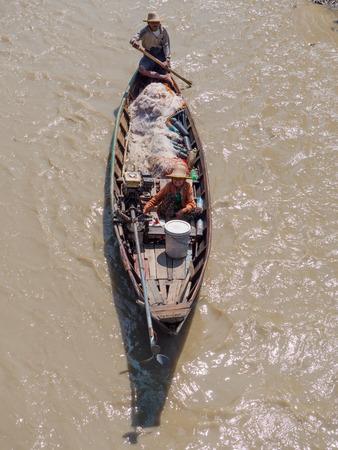 Dala, Myanmar - November 5, 2017: Small, traditional fishing vessel with husband and wife team padling down Dala River near Yangon.