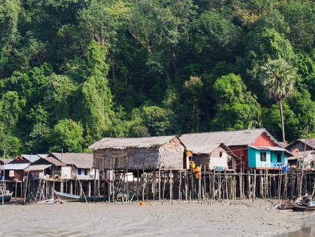Village along the canal through Kala Island outside Myeik, a part of the Mergui or Myeik Archipelago in the Tanintharyi Region of Southern Myanmar. The photo is taken at low tide. 스톡 콘텐츠