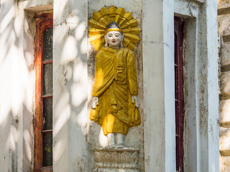 Standing Buddha image on old residential building in Yangon, Myanmar.