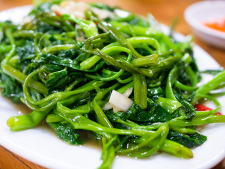 Vietnamese fried morning glory, rau muong xao toi. This is a popular dish across large parts of Asia, made with watercress or water spinach, chili pepper, garlic and fish sauce, oyster sauce or soy sauce. Stock Photo