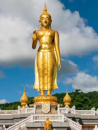 Golden standing Buddha at the peak at Hat Yai Municipality Park in Hat Yai, Songkhla Province in the south of Thailand.